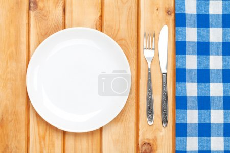 Photo for Empty plate, silverware and towel over wooden table background. View from above with copy space - Royalty Free Image