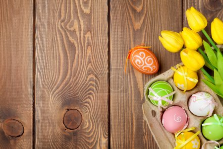 Photo for Easter background with colorful eggs and yellow tulips over wood. Top view with copy space - Royalty Free Image
