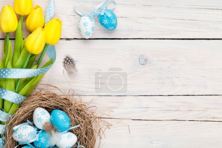 Photo for Easter background with blue and white eggs in nest and yellow tulips. Top view with copy space - Royalty Free Image