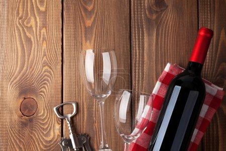 Photo pour Bouteille de vin rouge, verres et tire-bouchon sur fond de table en bois. Vue supérieure avec espace de copie - image libre de droit