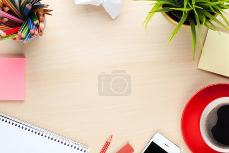 Office  table with supplies, coffee   and flower