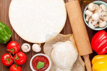 Photo for Pizza cooking ingredients. Dough, vegetables and spices. Top view with copy space - Royalty Free Image