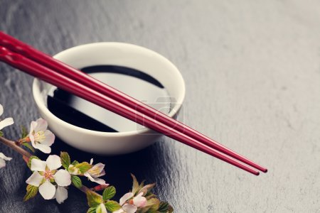 Photo for Japanese sushi chopsticks, soy sauce bowl and sakura blossom on black stone background. Top view with copy space. Toned - Royalty Free Image