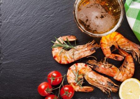 Photo pour Tasse à bière et crevettes grillées sur plaque de pierre. Vue supérieure avec espace de copie - image libre de droit