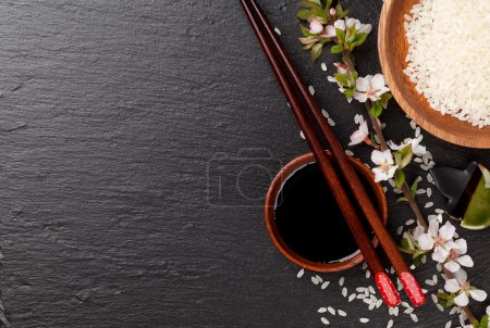 Photo for Japanese sushi chopsticks, soy sauce bowl, rice and sakura blossom on black stone background. Top view with copy space - Royalty Free Image