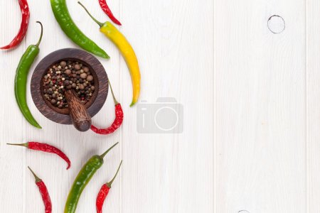 Photo for Colorful chili peppers and peppercorn on white wooden table. Top view with copy space - Royalty Free Image