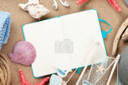 vacation notepad with items over sand