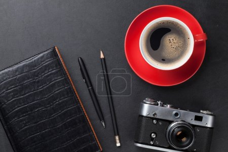 Desk with camera, supplies and coffee cup