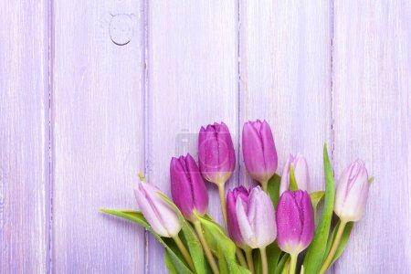 Photo pour Tulipes violettes sur table en bois. Vue supérieure avec espace de copie - image libre de droit