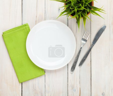 Photo for Empty plate and silverware over white wooden table background. View from above with copy space - Royalty Free Image