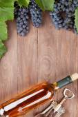 Wine bottle and grapes on garden table