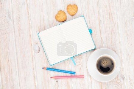 Photo pour Café, biscuits en forme de coeur et bloc-notes sur table en bois blanc avec espace de copie - image libre de droit