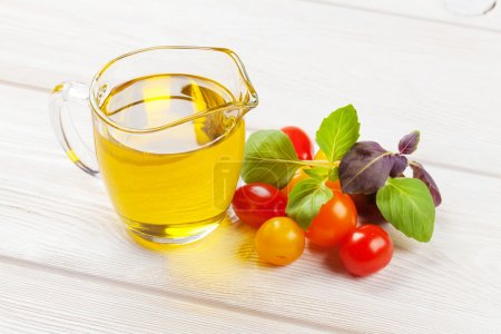 Olive oil, tomatoes, basil on table
