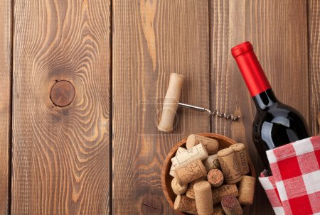 Photo for Red wine bottle, bowl with corks and corkscrew. View from above over rustic wooden table background with copy space - Royalty Free Image