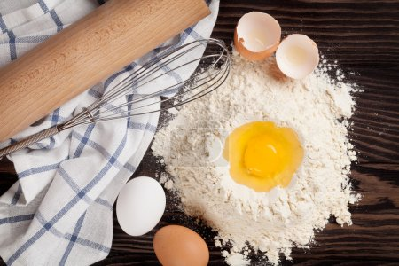 Photo for Kitchen table with utensils and ingredients. Flour and eggs. Top view - Royalty Free Image