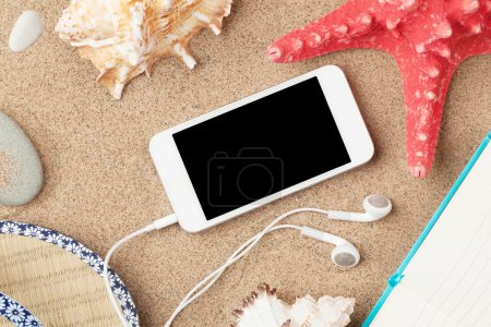 Smartphone and notepad on sea sand