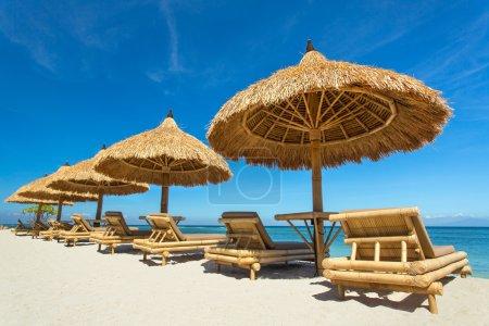 sillas de playa con sombrillas de paja