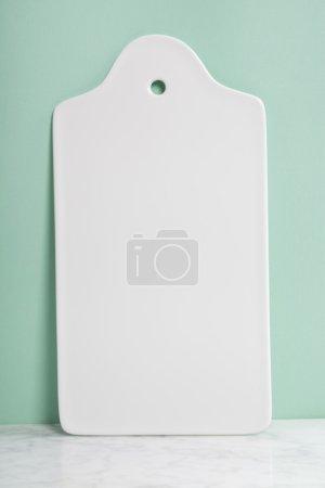 White ceramic serving board over light blue background