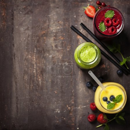 glasses of various smoothies with straws and fruits
