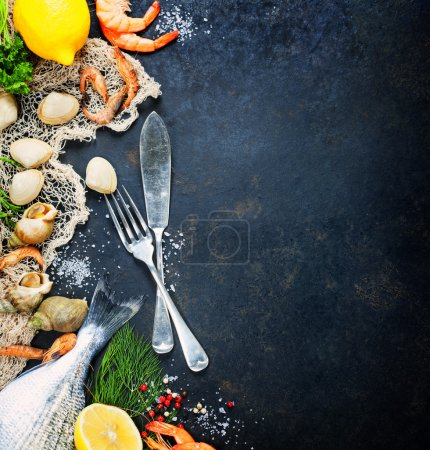 Photo for Delicious fresh fish and seafood on dark vintage background. Fish, clams and  shrimps with aromatic herbs, spices and vegetables - healthy food, diet or cooking concept - Royalty Free Image