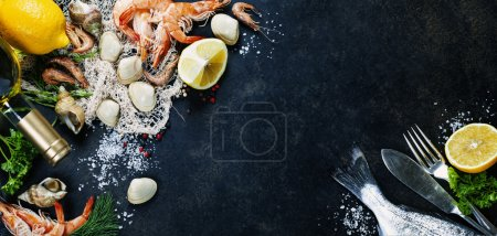 Foto de Delicious fresh fish and seafood on dark vintage background. Fish, clams and  shrimps with aromatic herbs, spices and vegetables - healthy food, diet or cooking concept - Imagen libre de derechos