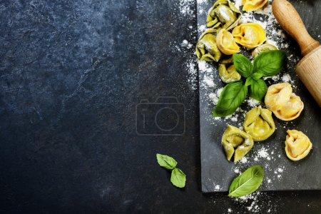 Photo pour Tortellini italien cru maison et feuilles de basilic sur fond vintage foncé - image libre de droit