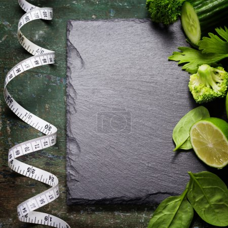 Fresh green vegetables and measuring tape