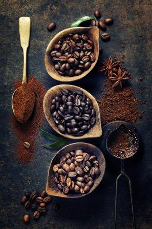 Photo pour Vue de dessus de trois différentes variétés de grains de café sur fond vintage noir - image libre de droit