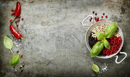 Photo for Overhead view of colourful dried pepper mix and basil in bowl on rustic background - Royalty Free Image