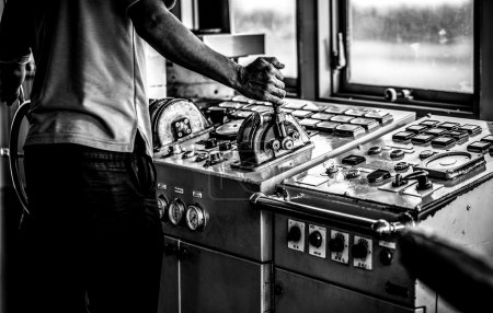 Captain's hands at a ferry steering wheel close-up. Black-white photo.