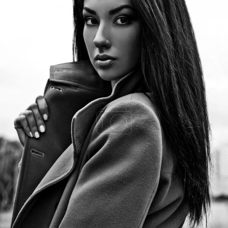 Black-white portrait of a beautiful fashionable woman on coat outdoor.