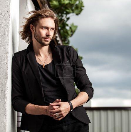 Elegant handsome man poses outdoor
