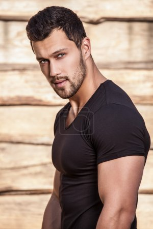 Portrait of young beautiful sporty man in t-shirt against wooden wall
