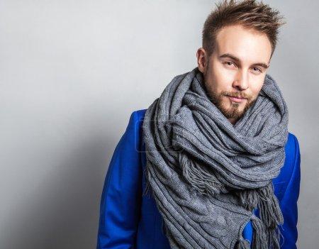 Elegant & Positive young handsome man in scarf. Studio fashion portrait.
