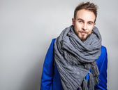 Elegant & Positive young handsome man in scarf. Studio fashion portrait.