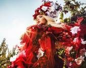 Fashion image of sensual girl in bright red fantasy stylization. Outdoor fairy tale art photo.