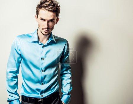 Photo pour Elégant jeune homme élégant en chemise de soie bleue. Studio portrait de mode . - image libre de droit
