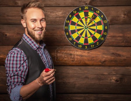Portrait of young friendly lucky man against old wooden wall with darts game. Concept: Hit in purpose. Photo.