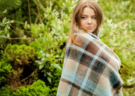 Outdoors portrait of beautiful young girl in casual white sweater & rolled in a plaid.