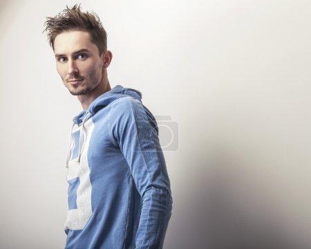 Photo pour Jeune homme attrayant dans une pose de pull de sport bleu en studio . - image libre de droit