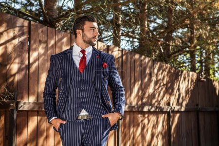 Photo for Elegant handsome man in classical blue suit poses near wooden fence. - Royalty Free Image