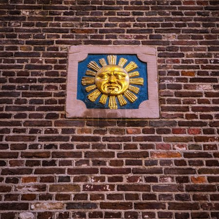 Symbolical images on an old brick wall of city building.