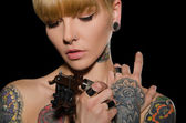 Tetovaný mladá žena s tetování stroj