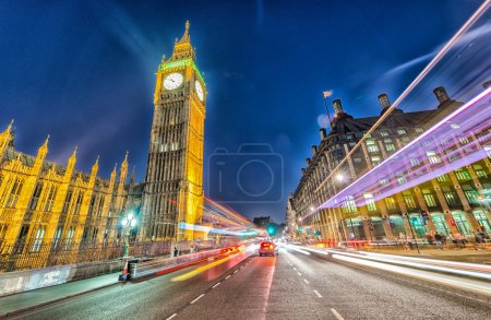 Westminster Bridge at night with cars speeding up - London