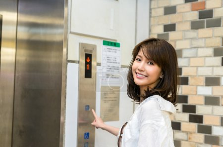young woman pushing button of elevator