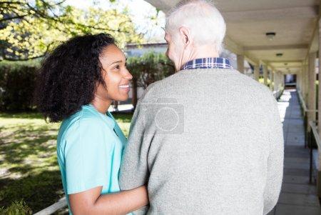 Nurse assisting elder man outdoor....