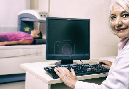 Senior female doctor scanning woman patient at bone densitometer