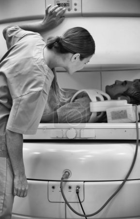 Female doctor reassuring male patient undergoing MRI