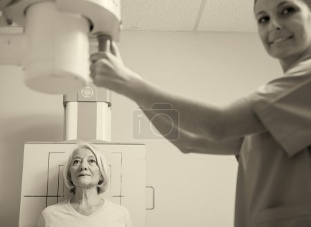 Senior woman undergoing ultrasound scan by young female doctor