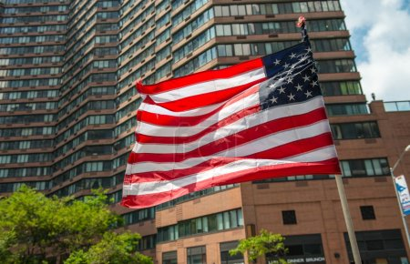 American flag waving with city building on background